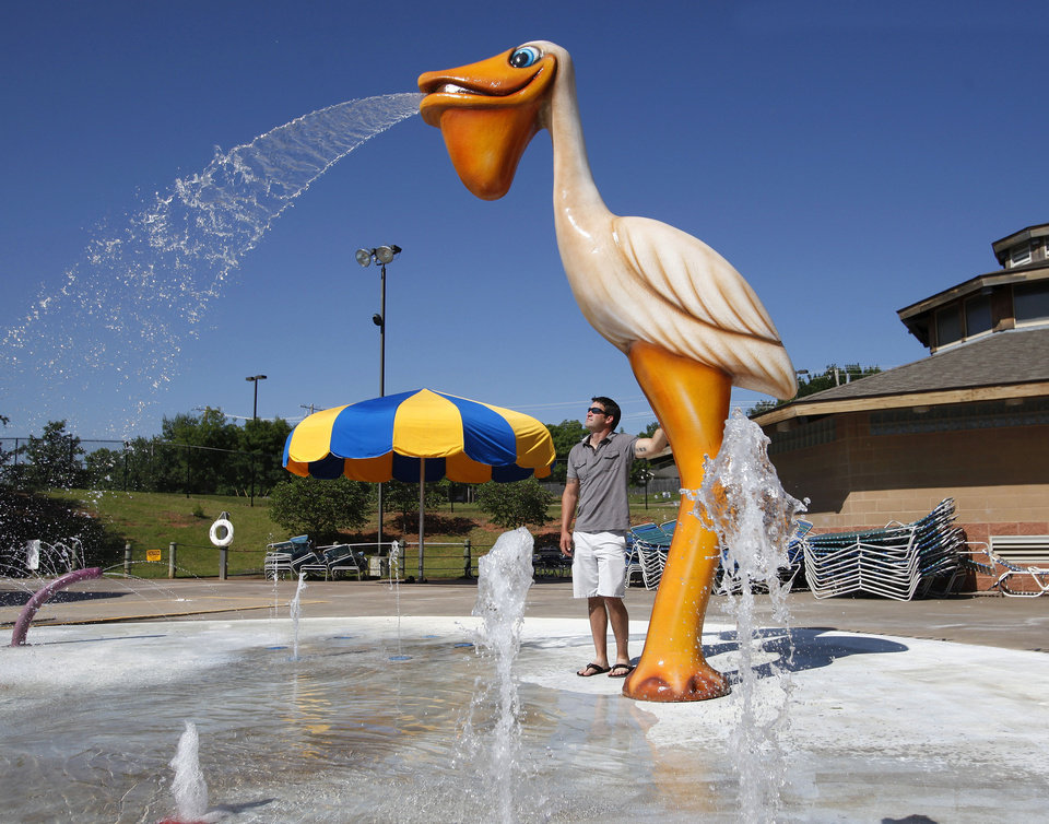 Photo - Jarad Prince stands under the new pelican shower at the Pelican Bay Aquatic Center on Wednesday.  Photo by Jim Beckel, THE OKLAHOMAN