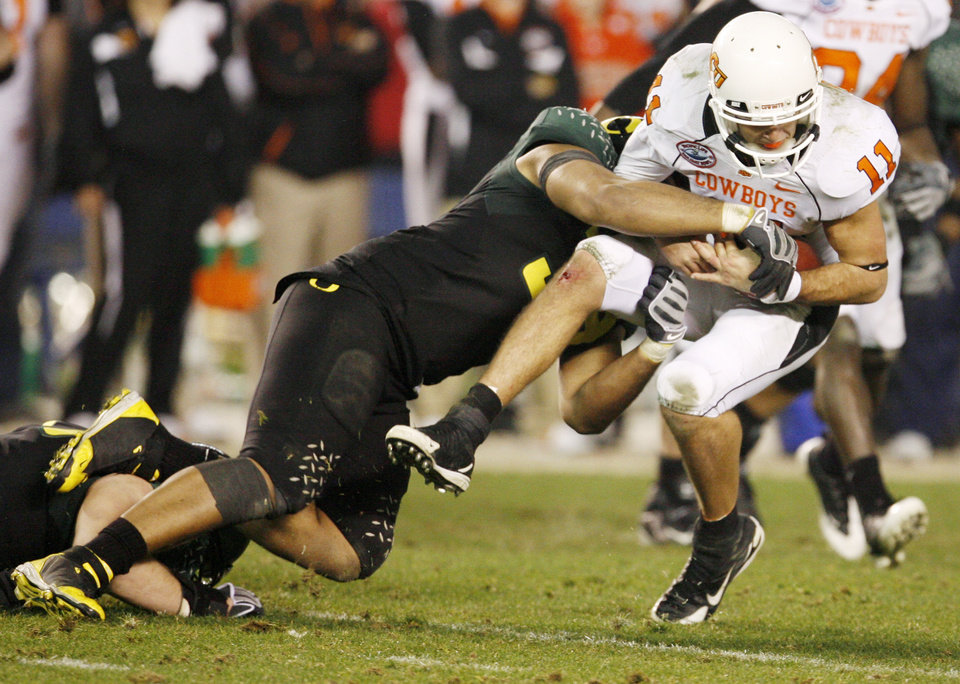 Photo - OSU's Zac Robinson (11) is sacked by Will Tukuafu (39) of Oregon in the fourth quarter of the Holiday Bowl college football game between Oklahoma State and Oregon at Qualcomm Stadium in San Diego, Tuesday, Dec. 30, 2008. Oregon won, 42-31. PHOTO BY NATE BILLINGS, THE OKLAHOMAN