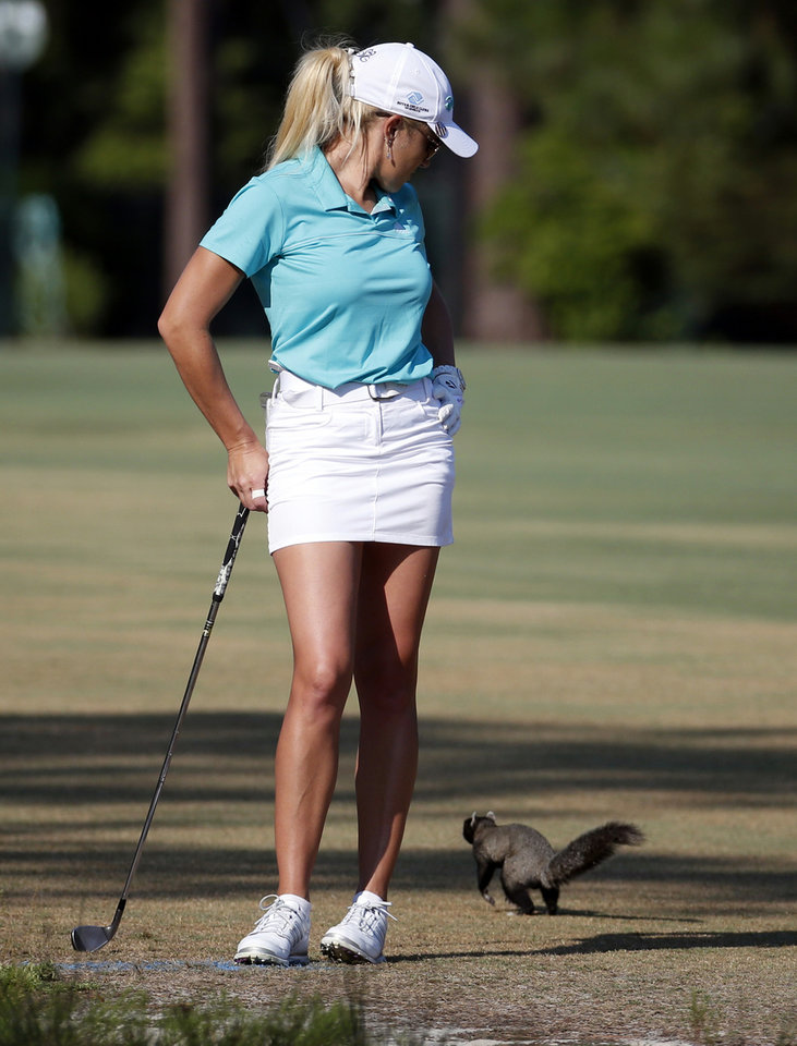 Photo - Natalie Gulbis watches a fox squirrel run past as she waits to hit her approach shot on the fourth hole during the first round of the U.S. Women's Open golf tournament in Pinehurst, N.C., Thursday, June 19, 2014. (AP Photo/John Bazemore)