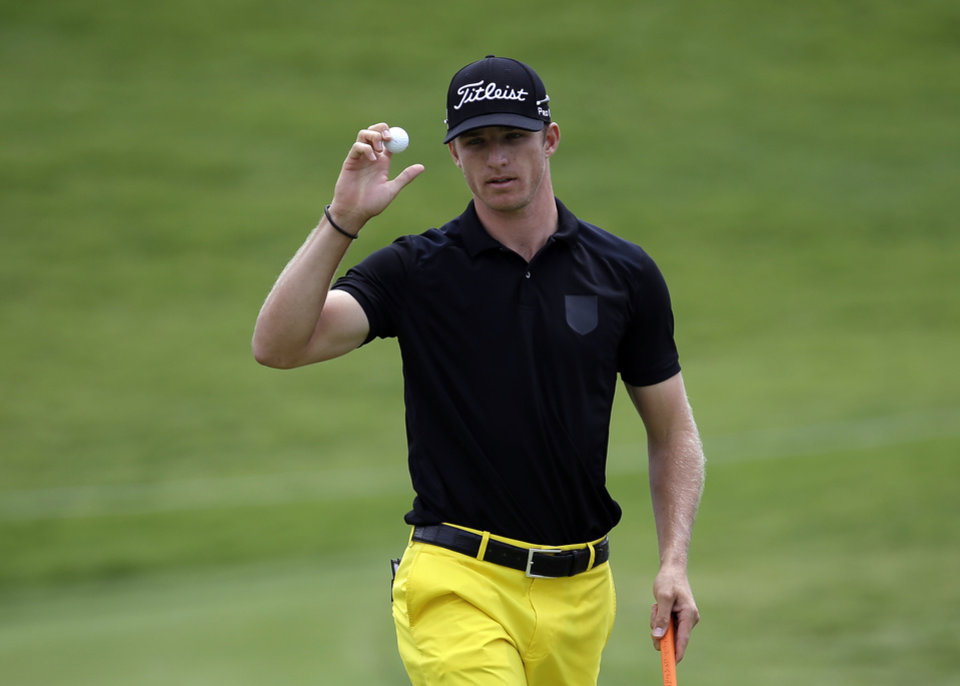 Photo - Morgan Hoffman acknowledges applause from the gallery after Hoffman sunk a putt on the first green during the third round of the Byron Nelson Championship golf tournament, Saturday, May 17, 2014, in Irving, Texas. (AP Photo/Tony Gutierrez)
