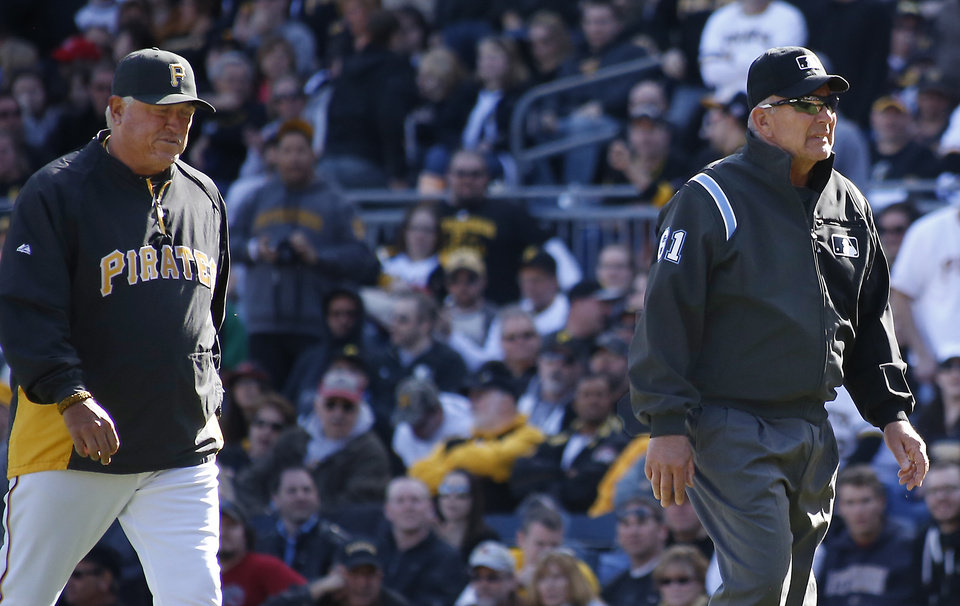 Photo - Pittsburgh Pirates manager Clint Hurdle, left, follows first base umpire Bob Davidson, from the field after he requested a review on a safe call at first on a pickoff attempt in the tenth inning of the opening day baseball game against the Chicago Cubs on Monday, March 31, 2014, in Pittsburgh. Cubs' Emilio Bonifacio was called safe but the call was overturned on the review requested by Hurdle and Bonifacio was ruled out. The Pirates won 1-0 in ten innings.(AP Photo/Keith Srakocic)