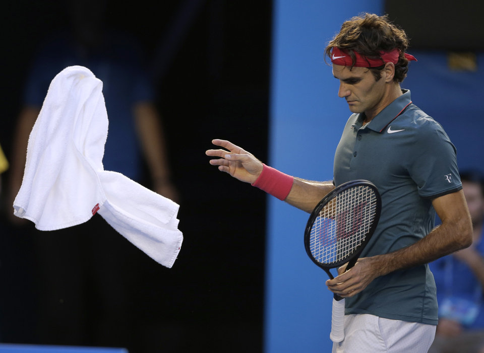Photo - Roger Federer of Switzerland throws a towel as he plays Andy Murray of Britain during their quarterfinal at the Australian Open tennis championship in Melbourne, Australia, Wednesday, Jan. 22, 2014.(AP Photo/Rick Rycroft)