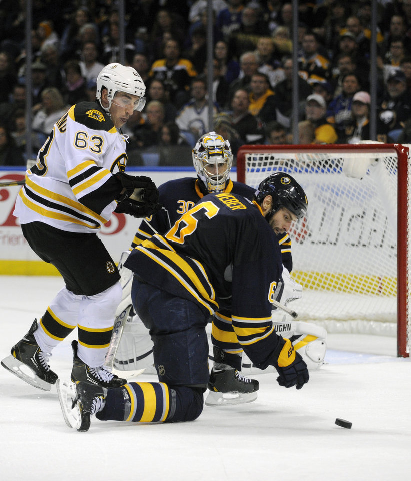 Photo - Boston Bruins left winger Brad Marchand (63) battles for the puck as Buffalo Sabres goaltender Ryan Miller (30) and defenseman Mike Weber (6) defend during the second period of an NHL hockey game in Buffalo, N.Y., Wednesday, Oct. 23, 2013. (AP Photo/Gary Wiepert)