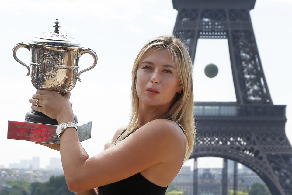 Photo - Russia's Maria Sharapova poses with the trophy in front of the Eiffel Tower, one day after defeating Romania's Simona Halep in the women's final of the French Open tennis tournament in Paris, France, Sunday, June 8, 2014. (AP Photo/Michel Euler)