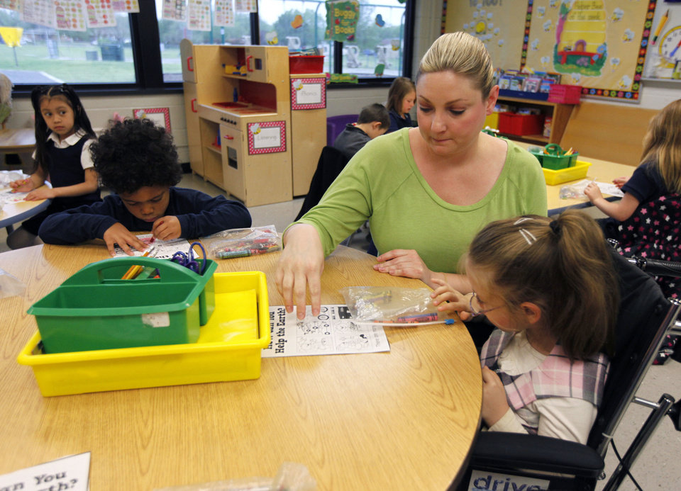 Photo - Lindsey Hanna helps special needs student McKiley Newlin as she spends part of her day in mainstream classrooms at Johnson Elementary School. Photo by Paul Hellstern, The Oklahoman  PAUL HELLSTERN - Oklahoman