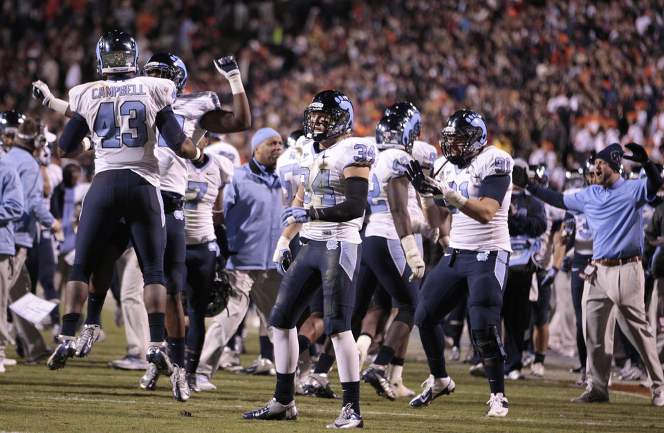 Photo -   North Carolina players celebrate a goal line stand during the second half of an NCAA college football game against Virginiaat Scott stadium on Thursday, Nov. 15, 2012 in Charlottesville, VA. North Carolina won the game 37-13. (AP Photo/Steve Helber)
