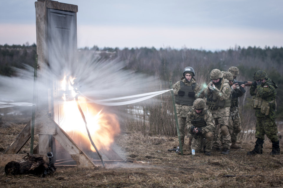 Photo -  Ukrainian combat training center engineers detonate an explosive charge to breach a door before entering a mock building as part of a training exercise in February with Canadian and U.S. engineers. About 250 Oklahoma National Guard soldiers are deployed to Ukraine as a part of a multinational training group designed to help the country withstand Russian aggression. [Photo by Sgt. Anthony Jones, 45th Infantry Brigade Combat Team]