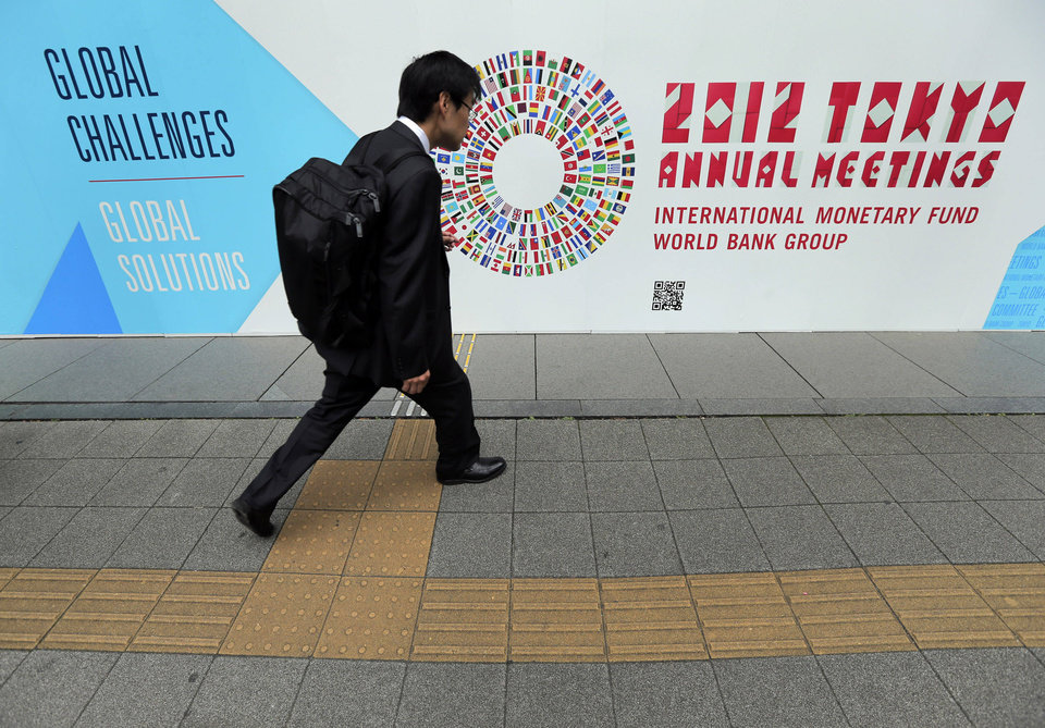 Photo -   FILE - In this Wednesday, Oct. 10, 2012, file photo, a man walks in front of the venue of the International Monetary Fund and World Bank meeting. When global finance ministers meet this week in Tokyo, they'll confront a triple challenge: Economic troubles in three major regions are threatening the world's economy. (AP Photo/Itsuo Inouye, File)
