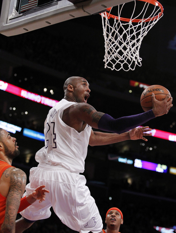Photo - Los Angeles Lakers guard Kobe Bryant (24) shoots a reverse lay up between New York Knicks center Tyson Chandler, left, and forward Carmelo Anthony, right, during the first half of their NBA basketball game in Los Angeles, Tuesday, Dec. 25, 2012. (AP Photo/Alex Gallardo)