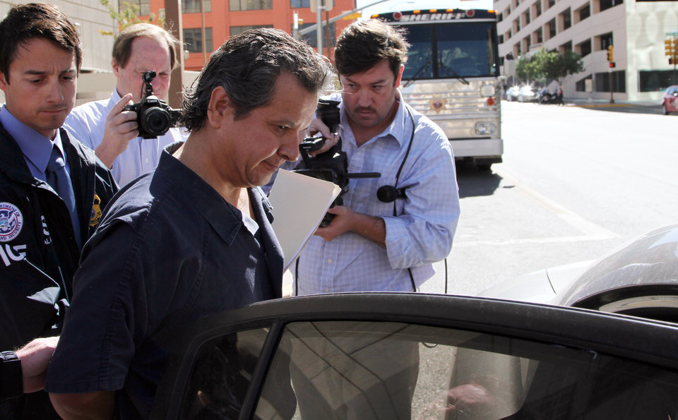 Photo -   Marco Antonio Delgado is placed into a car outside of the El Paso County Jail, Monday, Nov. 5, 2012 in El Paso, Texas. Delgado was arrested by Immigration and Customs Enforcement on charges of conspiracy to commit money laundering according to jail records. (AP Photo/Juan Carlos Llorca)