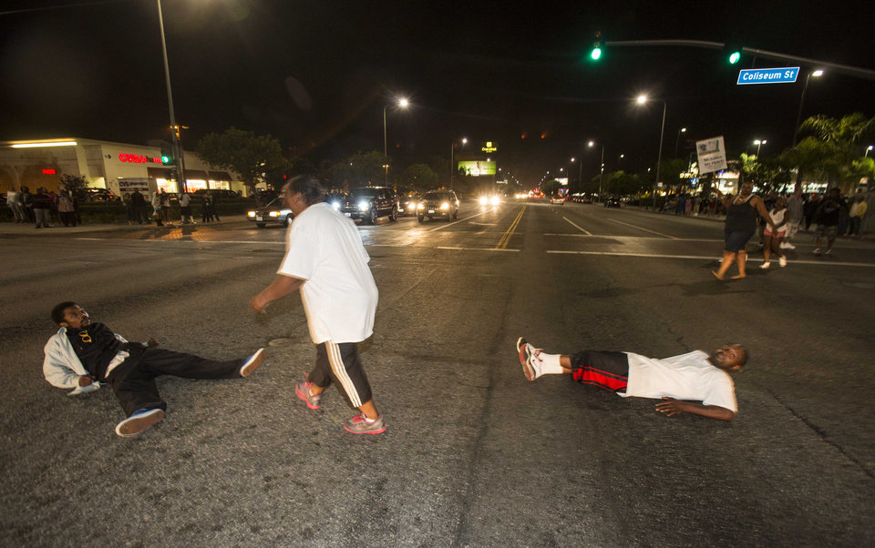 Photo - Demonstrators lay on the intersection of Crenshaw Boulevard and Coliseum street during a protest in Los Angeles on Sunday, July 14, 2013, the day after George Zimmerman was found not guilty in the shooting death of Trayvon Martin. Seventeen-year-old Martin was shot and killed in February 2012 by neighborhood watch volunteer George Zimmerman.  (AP Photo/Ringo H.W. Chiu)
