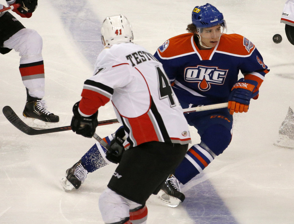 Photo - Tyler Pitlick with the Oklahoma City Barons eyes the puck beside Mike Testwuide of the Abbotsford Heat during an AHL hockey game at the Cox Convention Center in Oklahoma City, Friday, April 19, 2013. The Barons will take on the Charlotte Checkers in the first round of the Calder Cup playoffs. The best-of-5 Western Conference quarterfinal series starts in Oklahoma City at 7 p.m. Friday and Saturday at Cox Convention Center. Photo by Bryan Terry, The Oklahoman Archives  Bryan Terry - THE OKLAHOMAN