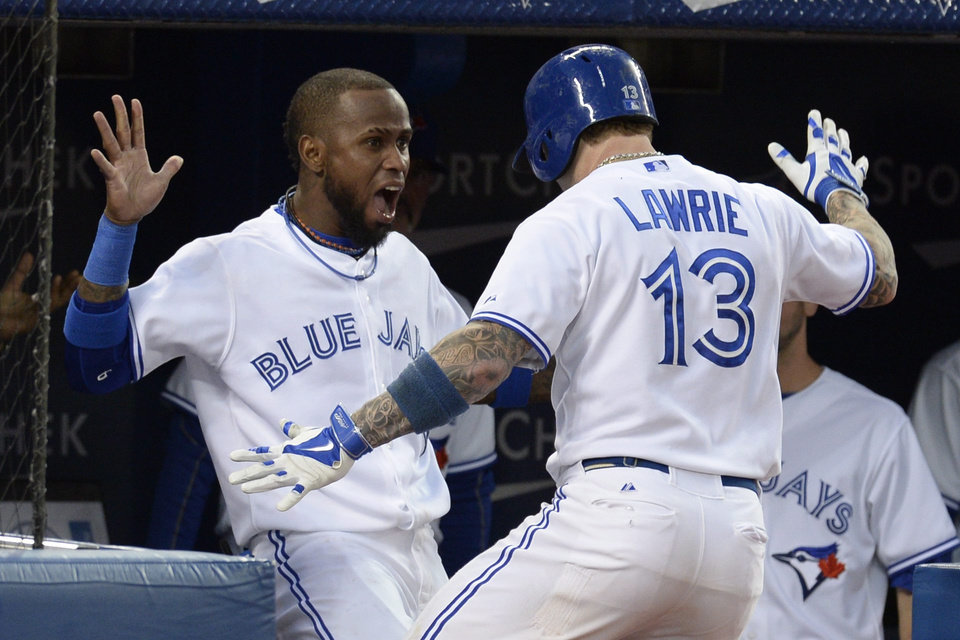 Photo - Toronto Blue Jays' Brett Lawrie, right, celebrates his solo home run with teammate Jose Reyes against the St. Louis Cardinals during the fifth inning of a baseball game in Toronto on Friday, June 6, 2014.  (AP Photo/The Canadian Press, Frank Gunn)