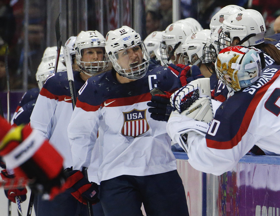 Photo - Meghan Duggan of the United States (10) is congratulated by teammates after scoring goal against Canada during the second period of the women's gold medal ice hockey game at the 2014 Winter Olympics, Thursday, Feb. 20, 2014, in Sochi, Russia. (AP Photo/Mark Humphrey)