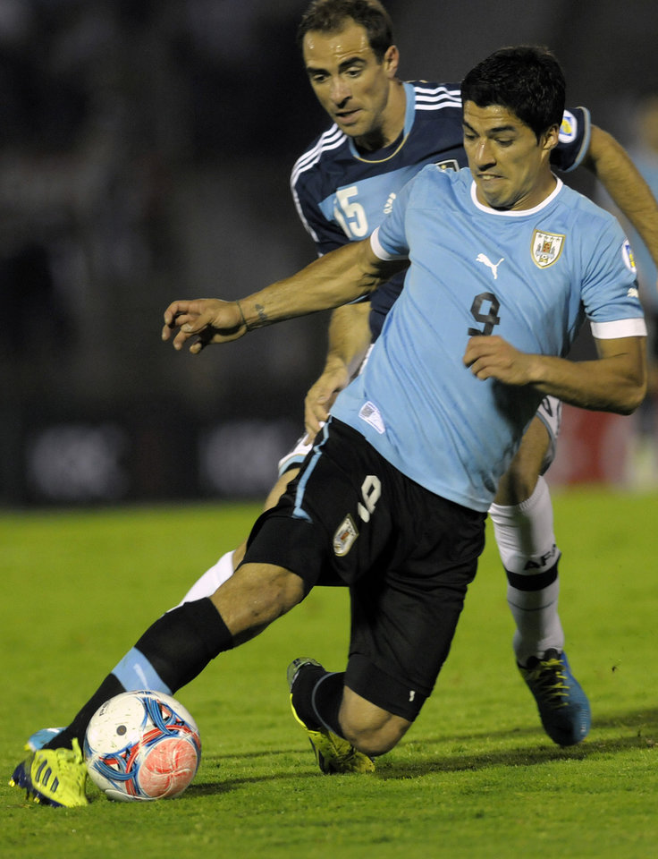 Photo - FILE - In this Oct. 15, 2013, file photo, Uruguay's Luis Suarez, front, fights for the ball during a 2014 World Cup qualifying soccer game in Montevideo. (AP Photo/Matilde Campodonico) - SEE FURTHER WORLD CUP CONTENT AT APIMAGES.COM