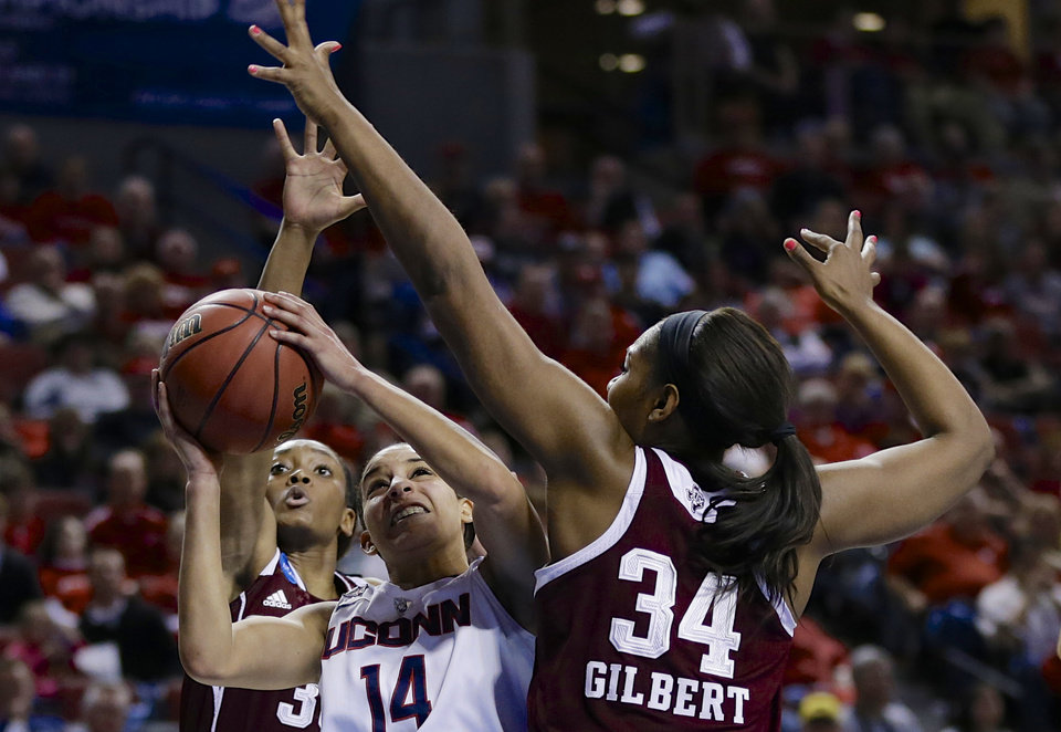 Photo - Connecticut's Bria Hartley (14) shoots against the defense of Texas A&M's Courtney Walker, rear, and Texas A&M's Karla Gilbert (34) during the first half of a regional final game in the NCAA college basketball tournament in Lincoln, Neb., Monday, March 31, 2014. (AP Photo/Nati Harnik)