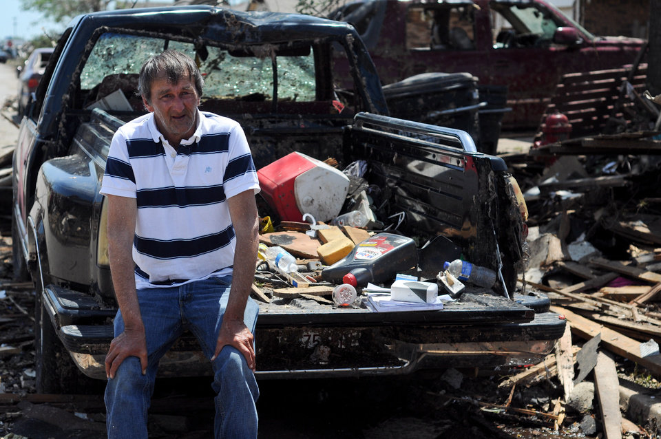 Photo - Freddy Roberts sits on the tailgate of his truck that was ruined by the tornado that struck Moore, Okla on May 20, 2013. Photo by KT King, The Oklahoman