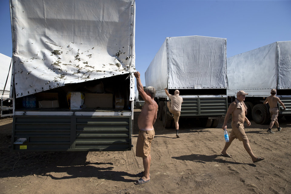 Photo - Drivers prepare to show cargos to journalists in a field where the aid convoy is parked in Voronezh, about 28 kilometers (17 miles) from Ukrainian border, Rostov-on-Don region, Russia, Friday, Aug. 15, 2014. The Ukrainian government threatened to use all means available to block the convoy if the Red Cross was not allowed to inspect the cargo. Such an inspection would ease concerns that Russia could use the aid shipment as cover for a military incursion in support of the separatists, who have come under growing pressure from government troops. (AP Photo/Pavel Golovkin)