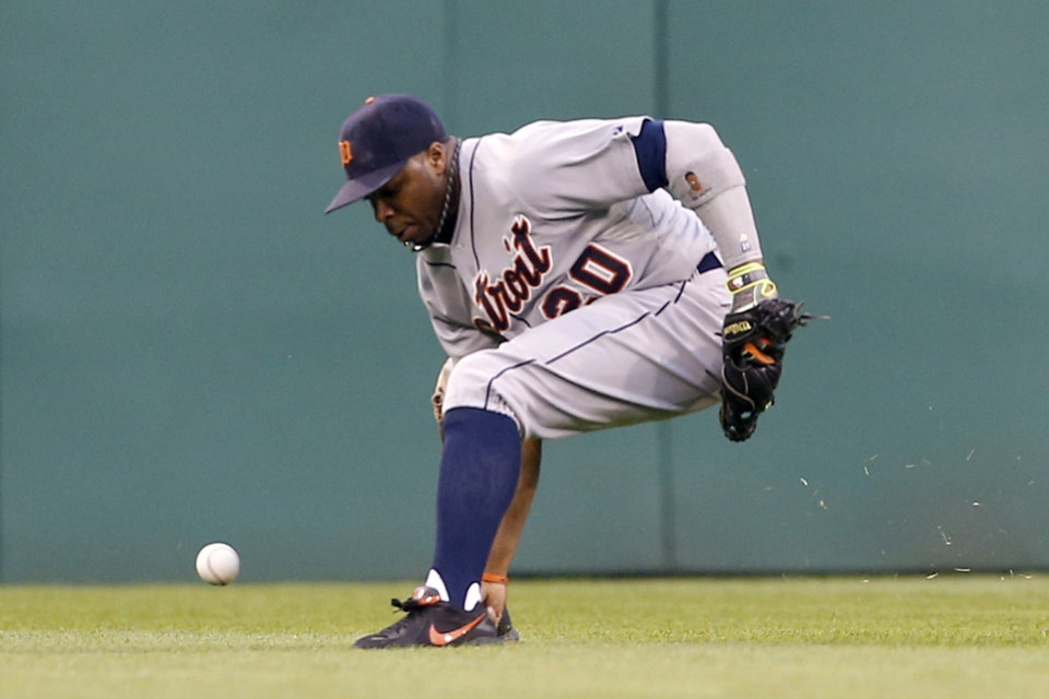 Photo - Detroit Tigers center fielder Rajai Davis kicks the ball away on a hit by Pittsburgh Pirates' Josh Harrison who got to second on the play in the first inning of the baseball game on Monday, Aug. 11, 2014, in Pittsburgh. (AP Photo/Keith Srakocic)