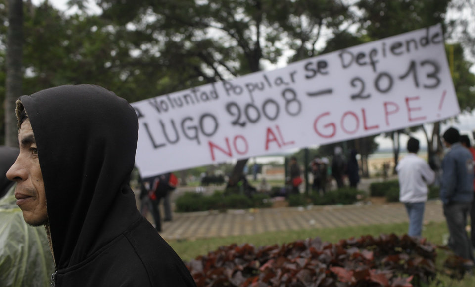 Photo -   Supporters of Paraguay's President Fernando Lugo gather outside Parliament, in Plaza de Armas, in protest to Lugo's impeachment trial, Asuncion, Paraguay, Friday, June 22, 2012. Paraguayan lawmakers voted Thursday to impeach Lugo for his role in a deadly clash involving landless farmers and police. Lugo's trial was to begin Friday in Paraguay's Senate. The banner in background reads in Spanish: