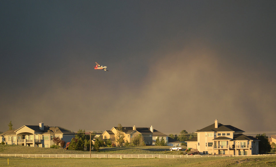 Photo - A slurry bomber flies over homes as it prepares to drop fire retardant on the Black Forest Fire in northeast of Colorado Springs on Tuesday, June 11, 2013. The fire consumed an estimated 7500 acres. It damaged 40-60 structures and forced the evacuation of thousands of people. As of Tuesday night the fire was reported as zero percent contained. (AP Photo/BryanOller)