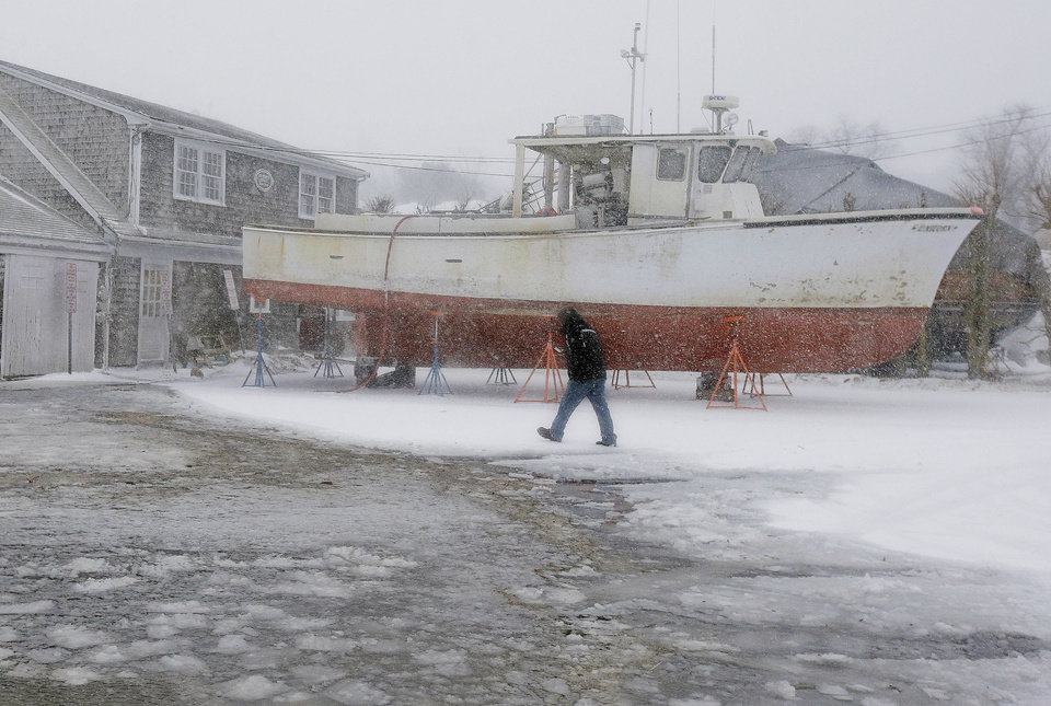 Photo - Ken Maynard, an employee at the Ryder's Cove Marina in Chatham, Mass., checks on the condition of the marina as high tide approaches Wednesday, March 26, 2014. A blizzard warning is in effect for Cape Cod, Martha's Vineyard and Nantucket as forecasters warned of wind gusts as high as 70 miles per hour with near-zero visibility at times. (AP Photo/Stephan Savoia)