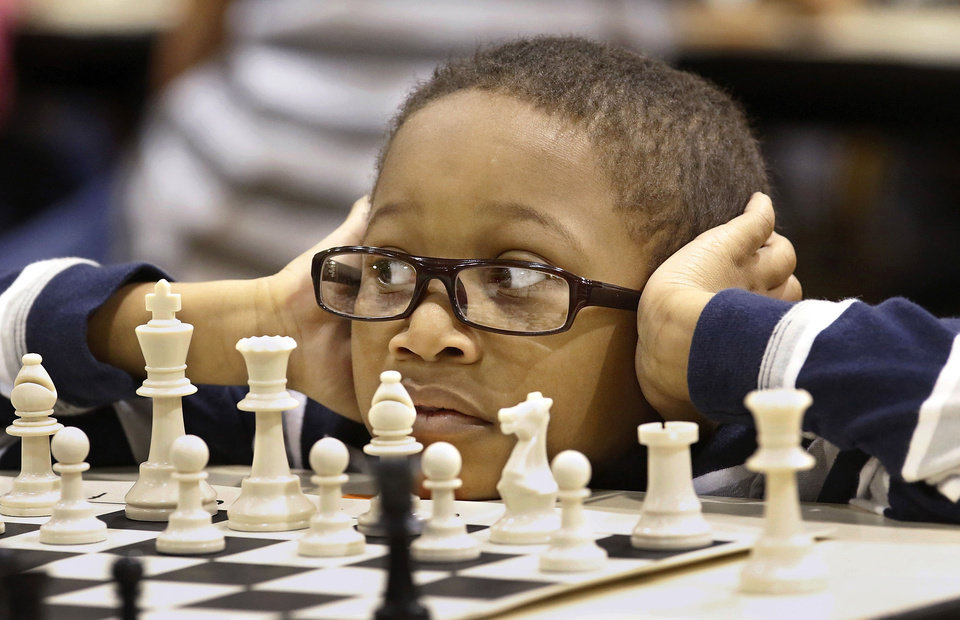 William Guesby, a second-grader at Highland Park Elementary School, waits for his opponent to make a move Saturday as more than 100 students from the elementary schools in the Midwest City-Del City School District competed against each other in a chess tournament, held in the gymnasium at Carl Albert High School. PHOTOS BY JIM BECKEL, THE OKLAHOMAN