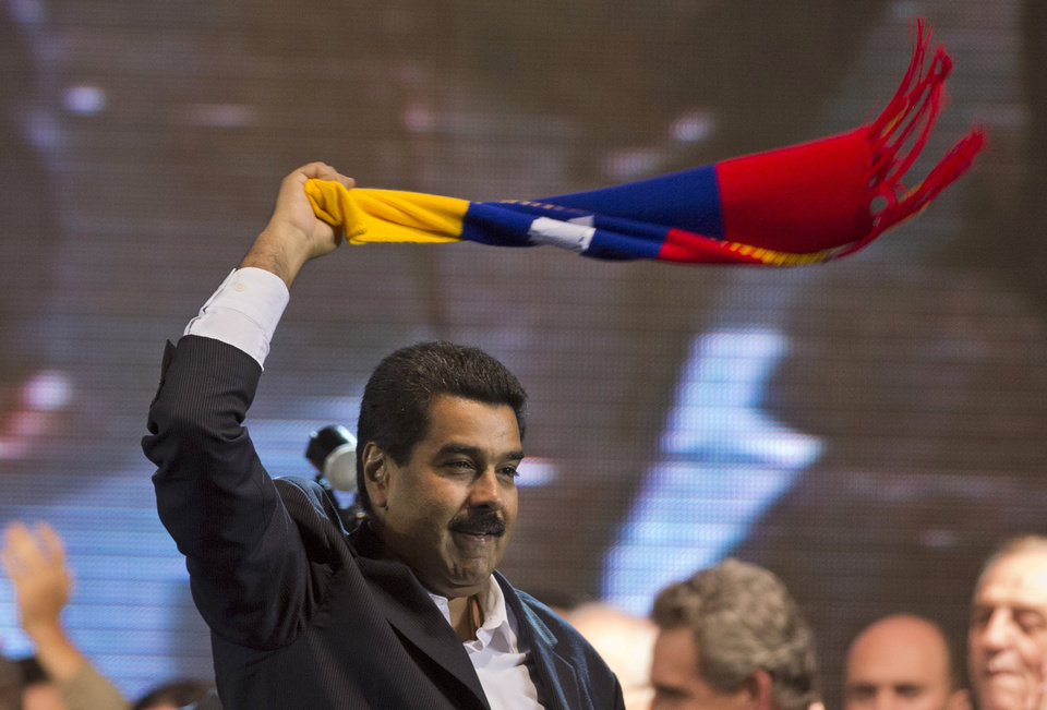 Photo - Venezuela's President Nicolas Maduro waves a scarf with the colors of the Venezuelan flag at a rally in Buenos Aires, Argentina, Wednesday, May 8, 2013. Maduro and his Argentine counterpart and ally, Cristina Fernandez, announced new energy and food agreements Wednesday, then Maduro cheered supporters of Argentina's president with a rousing speech at a soccer-stadium rally. (AP Photo/Victor R. Caivano)