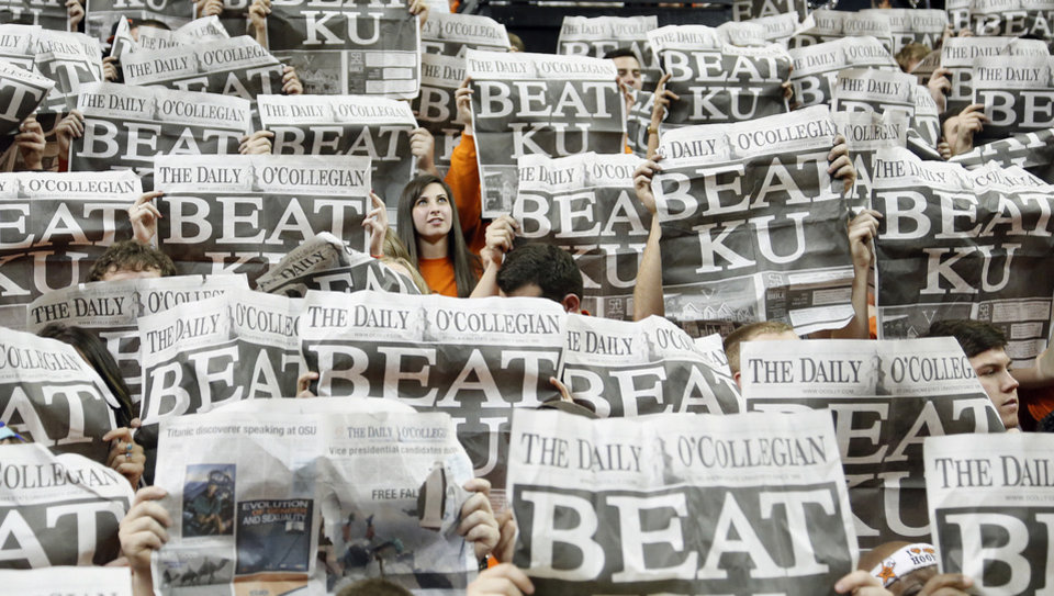 Photo - An Oklahoma State student is seen in the sea of newspaper during the college basketball game between the Oklahoma State University Cowboys (OSU) and the University of Kanas Jayhawks (KU) at Gallagher-Iba Arena on Wednesday, Feb. 20, 2013, in Stillwater, Okla. Photo by Chris Landsberger, The Oklahoman