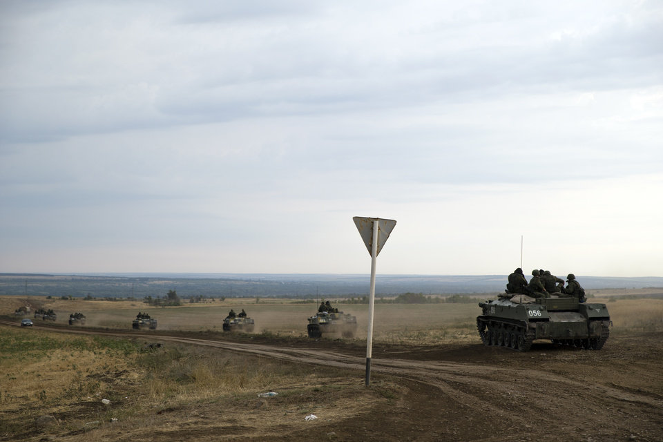 Photo - A number of Russian APC's move in a field in about 10 kilometers from the Russia-Ukrainian border control point near the town of  Donetsk, Rostov-on-Don region, Russia, Monday, Aug. 18, 2014. (AP Photo/Pavel Golovkin)