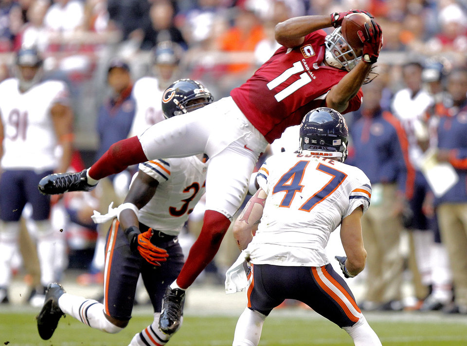 Photo - Arizona Cardinals wide receiver Larry Fitzgerald (11) leaps for a pass as Chicago Bears free safety Chris Conte (47) defends during the first half of an NFL football game, Sunday, Dec. 23, 2012, in Glendale, Ariz. (AP Photo/Paul Connors)