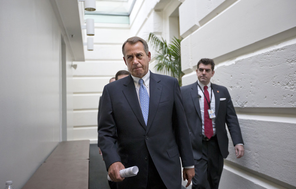 "FILE - In this Dec. 5, 2012, file photo, House Speaker John Boehner of Ohio walks to a closed-door Republican strategy session, Wednesday, Dec. 5, 2012, on Capitol Hill in Washington. Boehner has been caught up in a monumental struggle over taxes and spending aimed at keeping the country from taking a yearend dive over the ""fiscal cliff."" President Barack Obama is tugging Boehner one way in pursuit of a budget deal, while conservatives yank the other way, some howling that the speaker already is going wobbly on them and turning vindictive against those in his party who dare disagree.  (AP Photo/J. Scott Applewhite, File)"