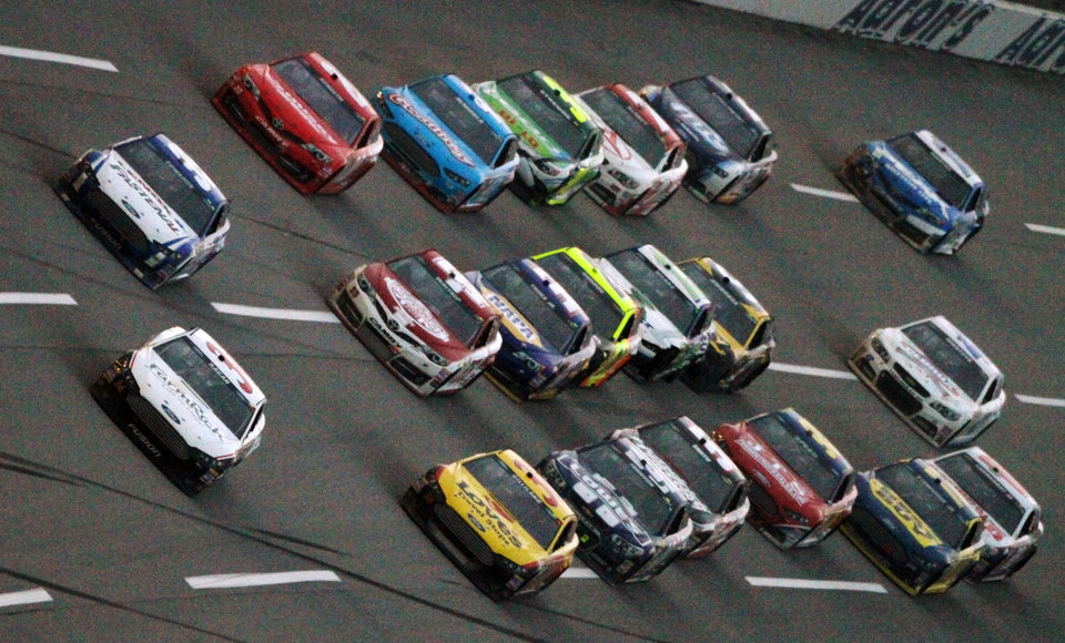 Photo - David Ragan, front, leads a pack of cars on the final lap to win the NASCAR Sprint Cup Series Aaron's 499 auto race at Talladega Superspeedway in Talladega, Ala., Sunday, May 5, 2013. (AP Photo/Jay Alley)
