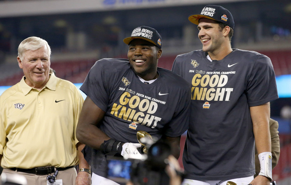 Photo - Central Florida head coach George O'Leary, left, watches as players Terrance Plummer, middle, and Blake Bortles, right, smile at the crowd and teammates after a Fiesta Bowl NCAA college football game win against Baylor Wednesday, Jan. 1, 2014, in Glendale, Ariz.  Central Florida defeated Baylor 52-42. (AP Photo/Ross D. Franklin)