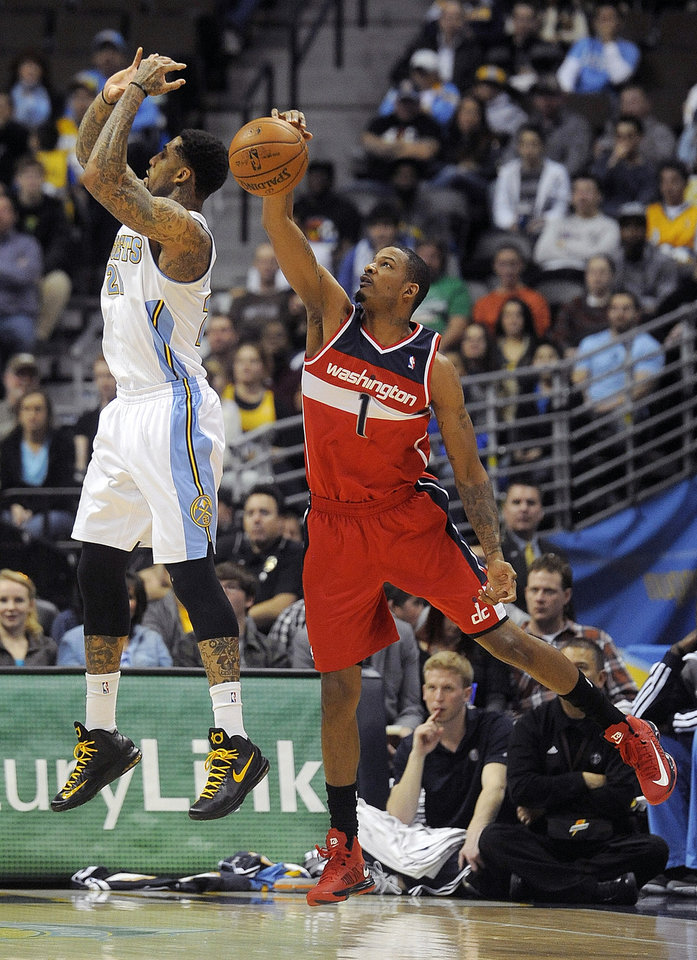 Washington Wizards forward Trevor Ariza, right, blocks a shot by Denver Nuggets guard Wilson Chandler, left, in the first quarter of an NBA basketball game on Friday, Jan. 18, 2013,  in Denver.  (AP Photo/Chris Schneider)