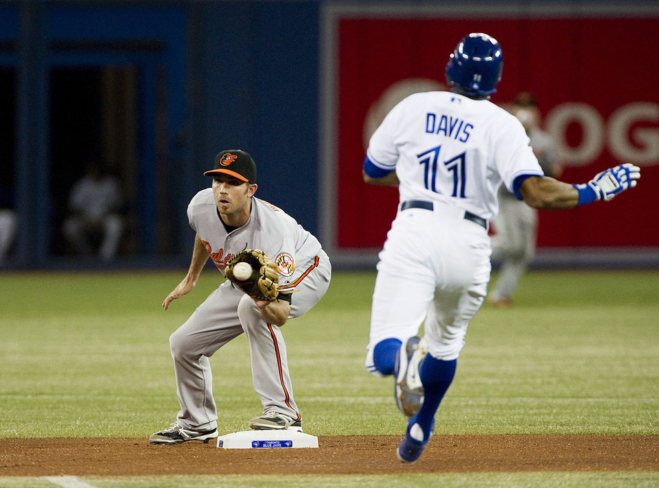 Photo -   Baltimore Orioles' J.J. Hardy, left, forces out Toronto Blue Jays' Rajai Davis during the first inning of a baseball game in Toronto, Tuesday, Sept. 4, 2012. (AP Photo/The Canadian Press, Aaron Vincent Elkaim)