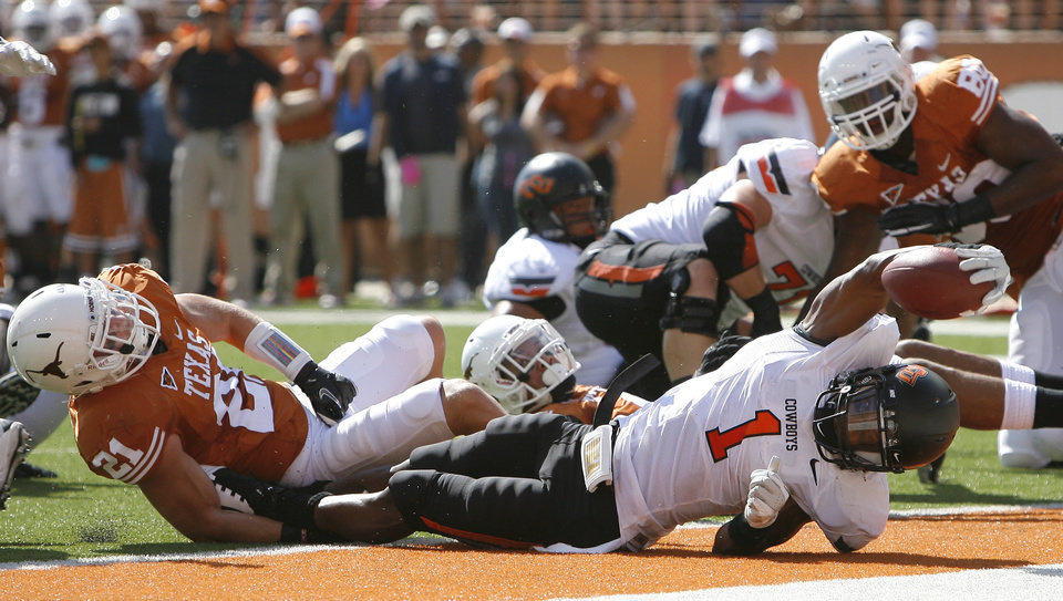 Photo - Oklahoma State's Joseph Randle (1) stretches for a touchdown as Texas' Blake Gideon (21) defends during first half of a college football game between the Oklahoma State University Cowboys (OSU) and the University of Texas Longhorns (UT) at Darrell K Royal-Texas Memorial Stadium in Austin, Texas, Saturday, Oct. 15, 2011. Photo by Sarah Phipps, The Oklahoman