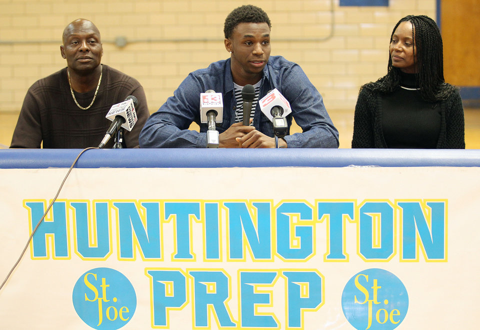 Photo - Huntington Prep basketball player Andrew Wiggins, center, flanked by his parents Mitchell Wiggins and Marita Payne-Wiggins, as he announces his commitment to the University of Kansas during a ceremony, Tuesday, May 14, 2013, at St. Joseph High School in Huntington W.Va. The Canadian star, a top prospect, averaged 23.4 points and 11.2 rebounds per game this season for West Virginia's Huntington Prep. (AP Photo/The Herald-Dispatch, Sholten Singer)