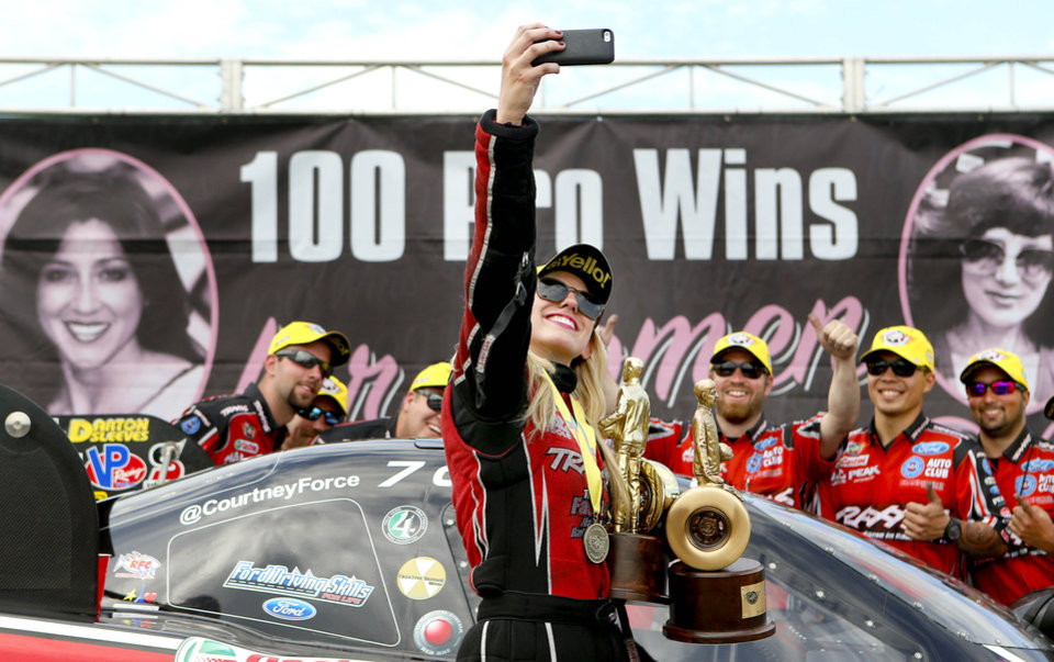Photo - Funny Car driver Courtney Force takes a selfie  photo with her team after winning the Kansas Nationals auto race and being the 100th professional win for women drivers in the NHRA on Sunday, May 25, 2014, at Heartland Park in Topeka, Kan. (AP Photo/The Topeka Capital Journal, Chris Neal)