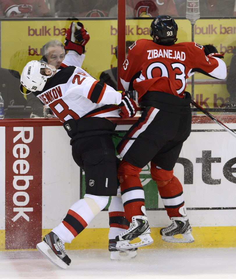 Photo - New Jersey Devils defenseman Anton Volchenkov,left,  collides with Ottawa Senators center Mika Zibanejad, right, along the boards during first period NHL action in Ottawa, on Monday March 25, 2013.  (AP Photo/The Canadian Press, Adrian Wyld)