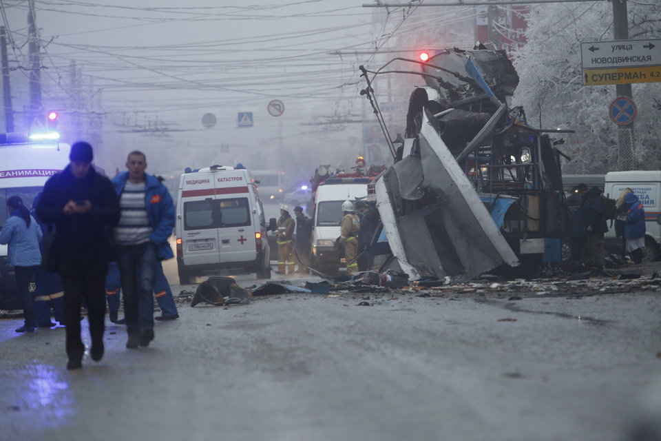 Photo - Ambulances line up a site of a trolleybus explosion, background, in Volgograd, Russia Monday, Dec. 30, 2013.  A bomb blast tore through the trolleybus in the city Volgograd on Monday morning, killing at least 10 people a day after a suicide bombing that killed at 17 at the city's main railway station. (AP Photo/Denis Tyrin)