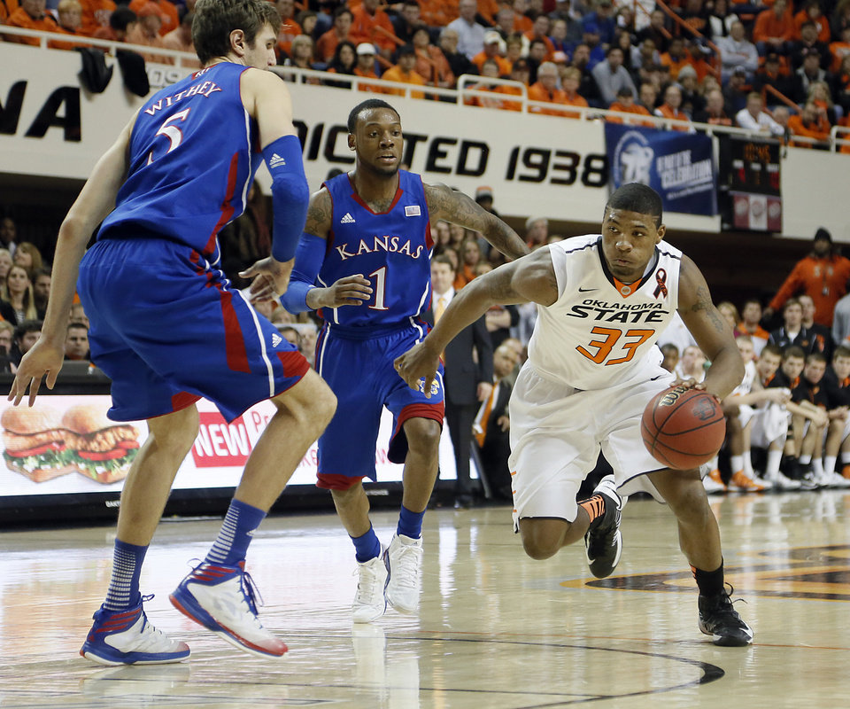 Oklahoma State 's Marcus Smart (33) drives past Kansas' Jeff Withey (5) and Naadir Tharpe (1) during the college basketball game between the Oklahoma State University Cowboys (OSU) and the University of Kanas Jayhawks (KU) at Gallagher-Iba Arena on Wednesday, Feb. 20, 2013, in Stillwater, Okla. Photo by Chris Landsberger, The Oklahoman