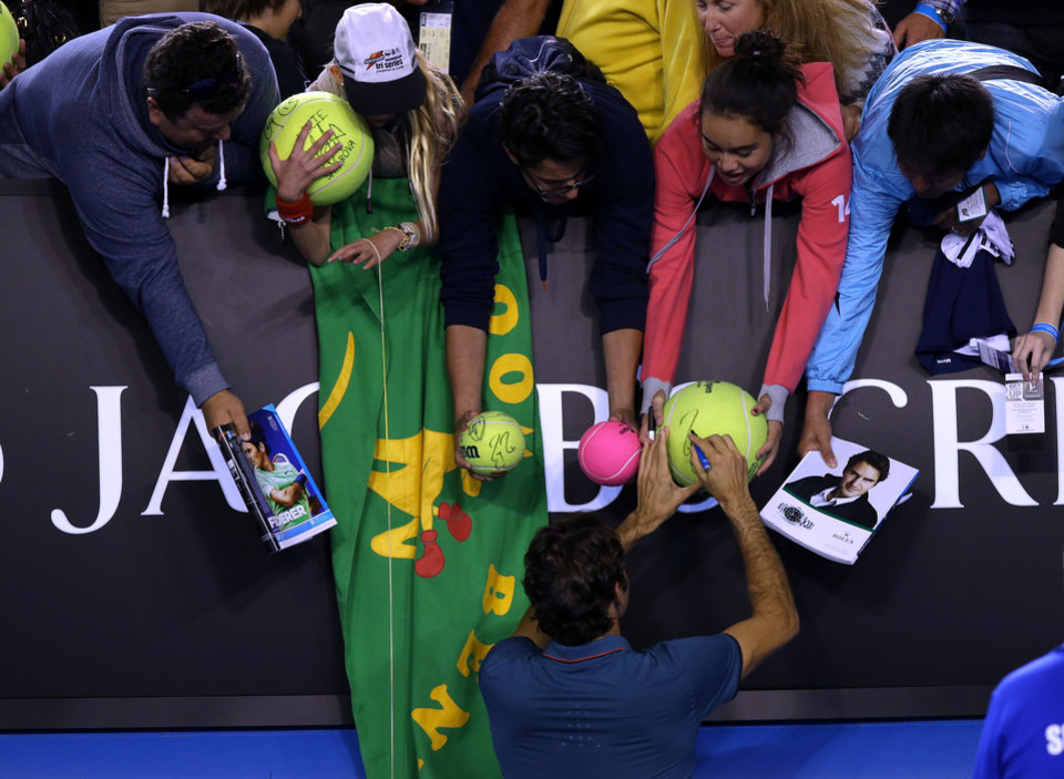 Photo - Roger Federer of Switzerland signs autographs for fans after defeating Andy Murray of Britain in their quarterfinal at the Australian Open tennis championship in Melbourne, Australia, Wednesday, Jan. 22, 2014.(AP Photo/Aaron Favila)