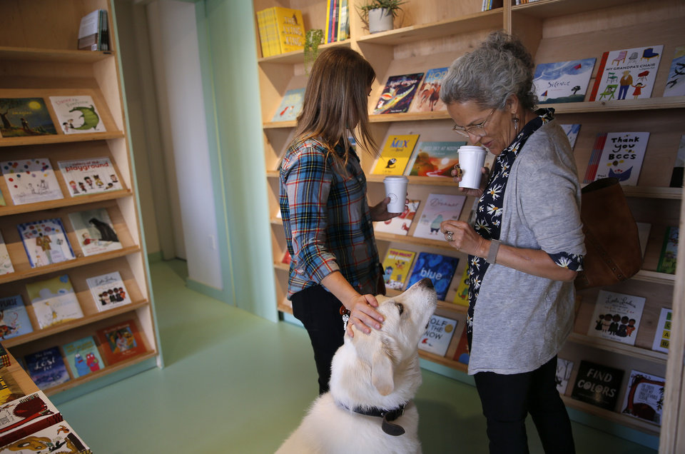 Photo -  Espanta Steppe, right, and Michelle Lavasque pet Boz in the bookstore at The Kitchen at Commonplace Books in Midtown. [Photo by Sarah Phipps, The Oklahoman]