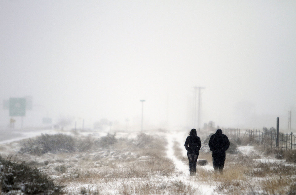 Jennifer Maez, left, and Jared Romero go out for a stroll in the snow on the Frontage Road along I-25 near Santa Fe, N.M. Thursday, Dec. 5, 2013.  A storm system swept through parts of New Mexico early Thursday, dumping up to 6 inches of snow across the state and causing highway headaches, school closures and delays. (AP Photo/The Santa Fe New Mexican, Luis Sanchez Saturno)