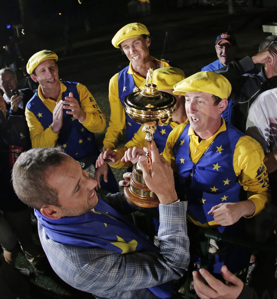 Photo - Europe's Sergio Garcia shows the trophy to some fans after winning the Ryder Cup PGA golf tournament Sunday, Sept. 30, 2012, at the Medinah Country Club in Medinah, Ill. (AP Photo/Charlie Riedel)  ORG XMIT: PGA271