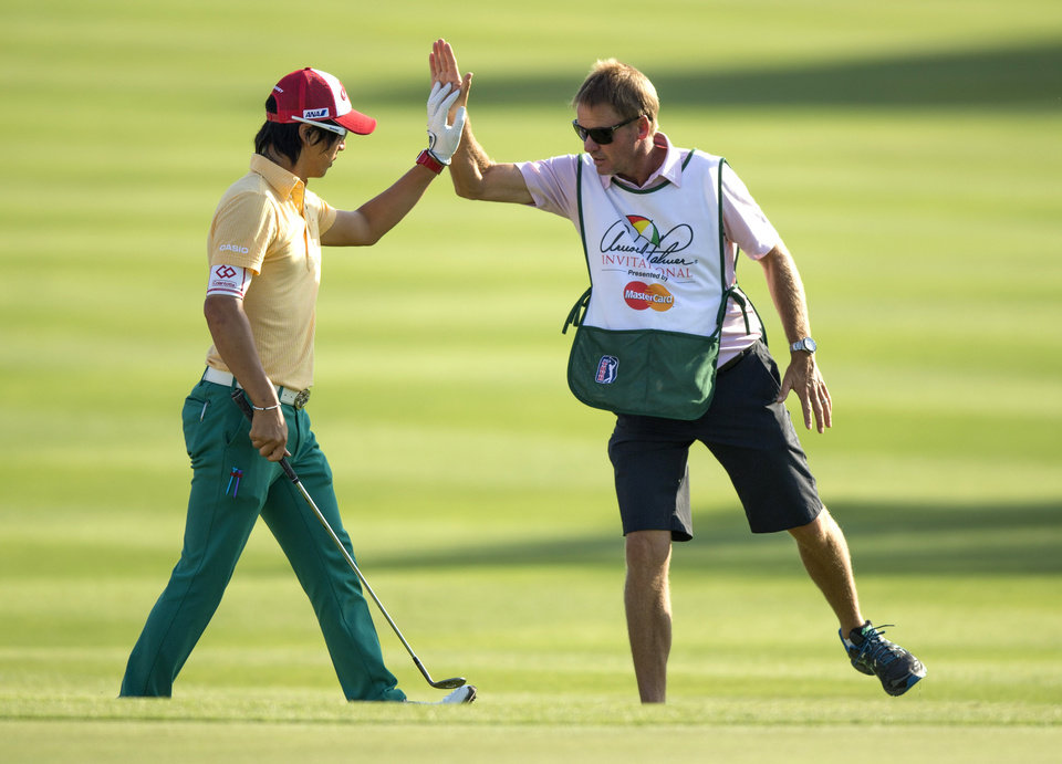 Photo - Ryo Ishikawa, left, of Japan, high-fives his caddie Simon Clarke after chipping the ball into the cup for a birdie on the 15th hole during the second round of the Arnold Palmer Invitational golf tournament at Bay Hill Friday, March 21, 2014, in Orlando, Fla. (AP Photo/ Willie J. Allen Jr.)