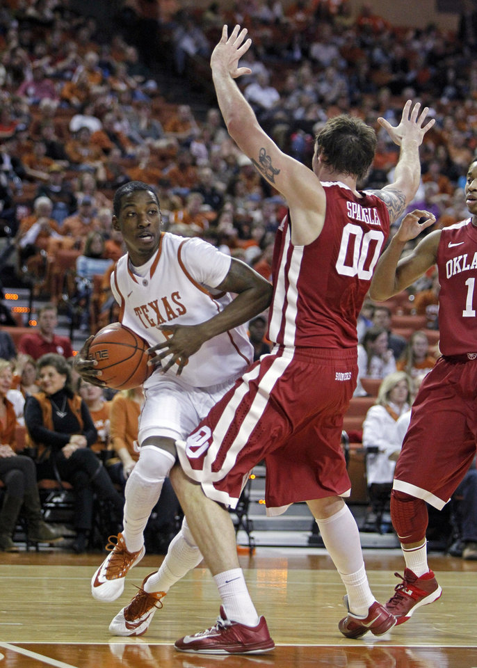 Photo - Texas guard Damarcus Croaker (5) attempts to drive around Oklahoma forward Ryan Spangler (00) during the first half of an NCAA college basketball game, Saturday, Jan. 4, 2014, in Austin, Texas. (AP Photo/Michael Thomas)