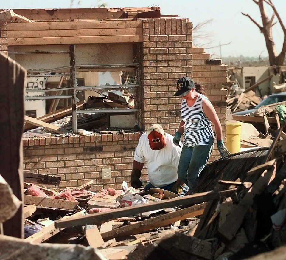 Tornado damage: Unidentified couple searches through rubble in a home destroyed in Monday night's tornado in the Del Aire housing addition Saturday prior to arrival of the President.