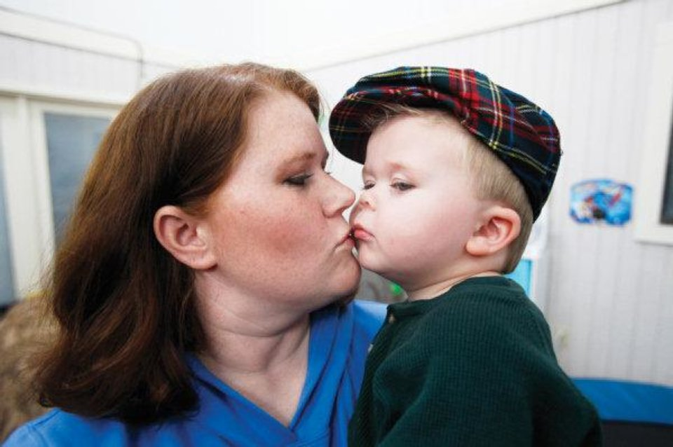 Photo - Candi Smithson kisses her son, Preston, 2, at their home in Yukon on Wednesday. Preston has celiac disease, which prevents him from eating anything containing gluten. Photos by Steve Gooch, The Oklahoman